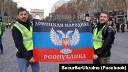 Сьцяг групоўкі «ДНР» падчас пратэстаў у сталіцы Францыі. Паводле дадзеных СБУ, яго трымаюць Сарлін Фабры іКсаўе Мара