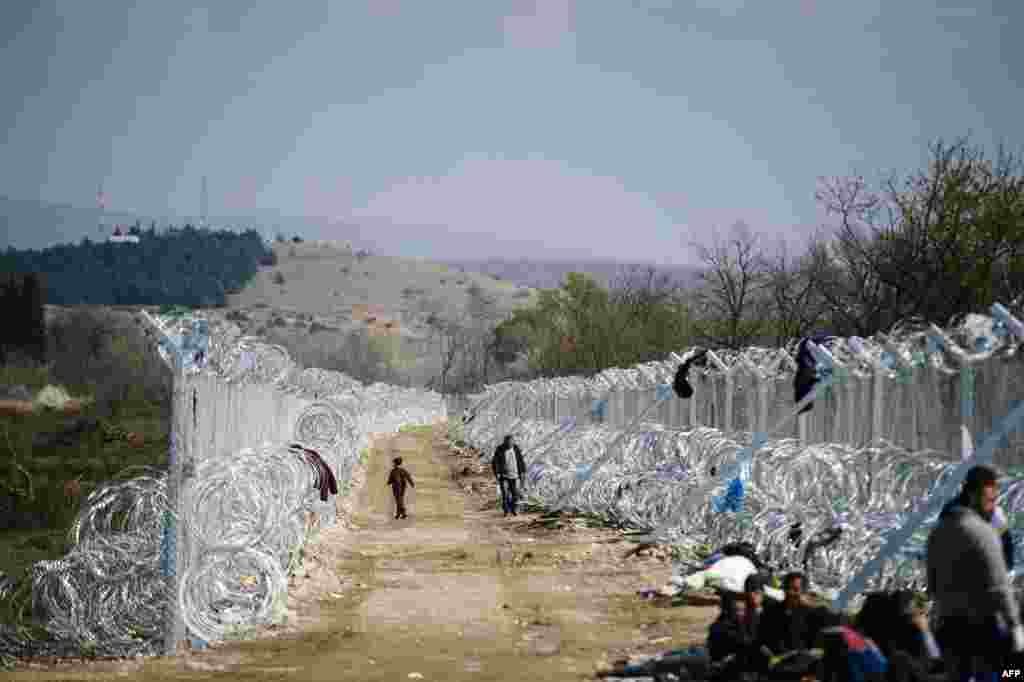 Migrants and refugees walk on a path by a fence and razor wire at the Greek-Macedonian border, near the Macedonian town of Gevgelija. (AFP/Dimitar Diloff)