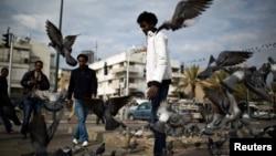 Архивска фотографија: Африкански мигранти ранат голуби во паркот Левински во Тел Авив на 9 јануари 2014 година