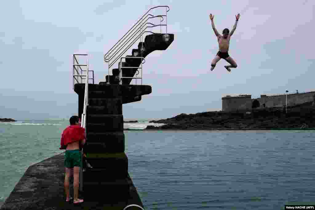 Youngsters jump into the sea from a diving platform in Saint-Malo, northwestern France. (AFP/Valery Hache)