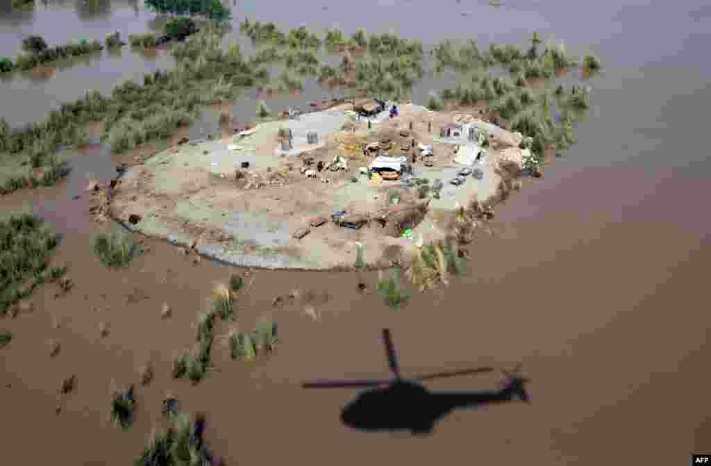 The shadow of a Pakistani Army helicopter is seen next to land surrounded by floodwaters where affected villagers gathered to seek higher ground in the Rajanpur district, in Punjab Province, on August 6. (AFP/SS Mirza)