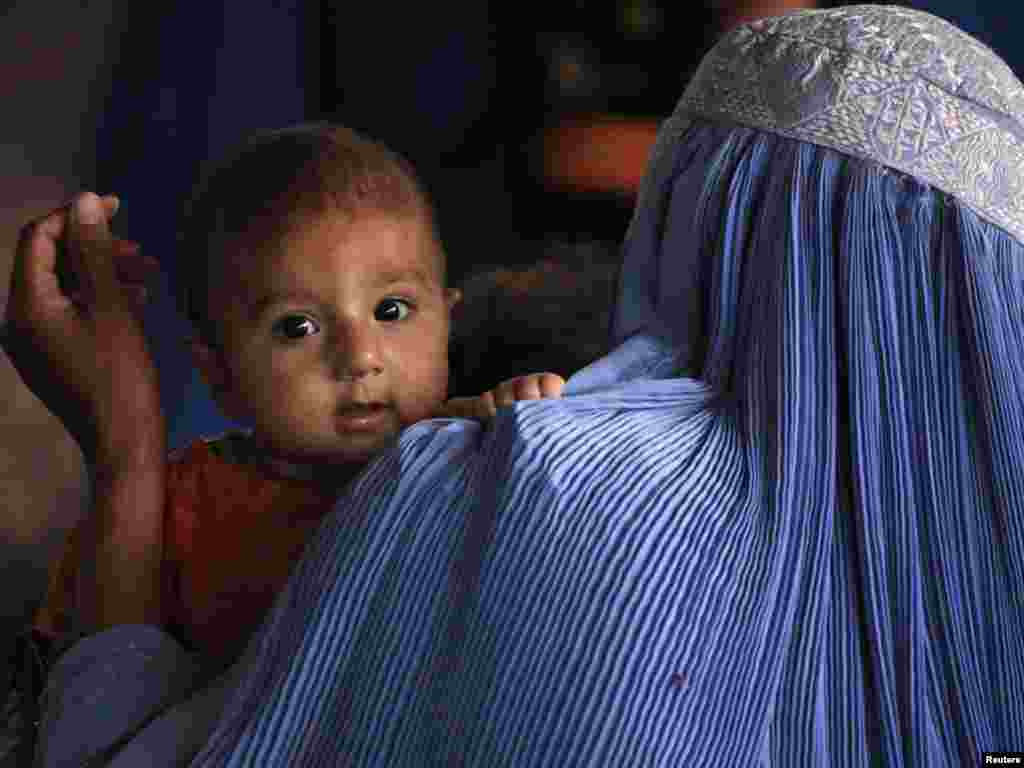 An Afghan woman holds her child as she waits in line at a repatriation center on the outskirts of Peshawar, Pakistan. Photo by Fayaz Aziz for Reuters.