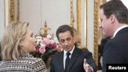 French President Nicolas Sarkozy (center) and British Prime Minister David Cameron (right) will host the Paris conference on Libya, which U.S. Secretary of State Hillary Clinton will also attend.