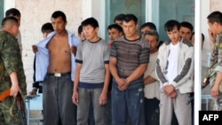 Police officers search detained ethnic Uzbeks in the village of Nariman on June 21