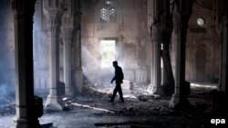 A man walks inside the burnt Rabaa Al-Adawiya Mosque, the morning after the clearing of the sit-in in and around the mosque in Cairo by police in which scores were killed.