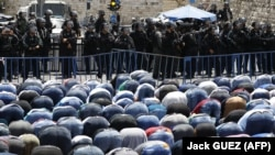 Israeli riot police keep watch as Palestinian Muslim worshippers pray outside Jerusalem's old city on July 28, 2017.