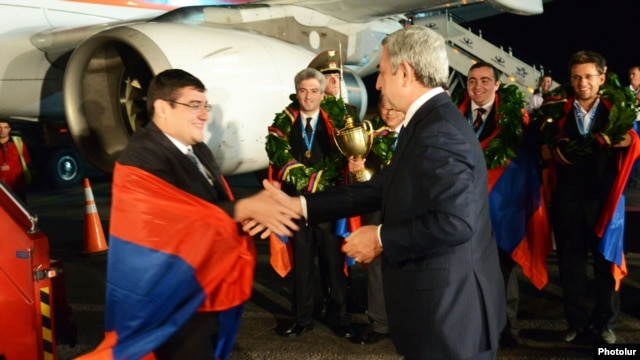 Armenian President Serzh Sarkisian (right) greets members of the Armenian men's chess team at Yerevan's Zvartnots airport.