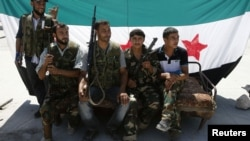 Озод Сурия армияси жангчилари Сурия мухолифати байроғи олдида, Алеппо ш., 2012 йил 3 сентябр.