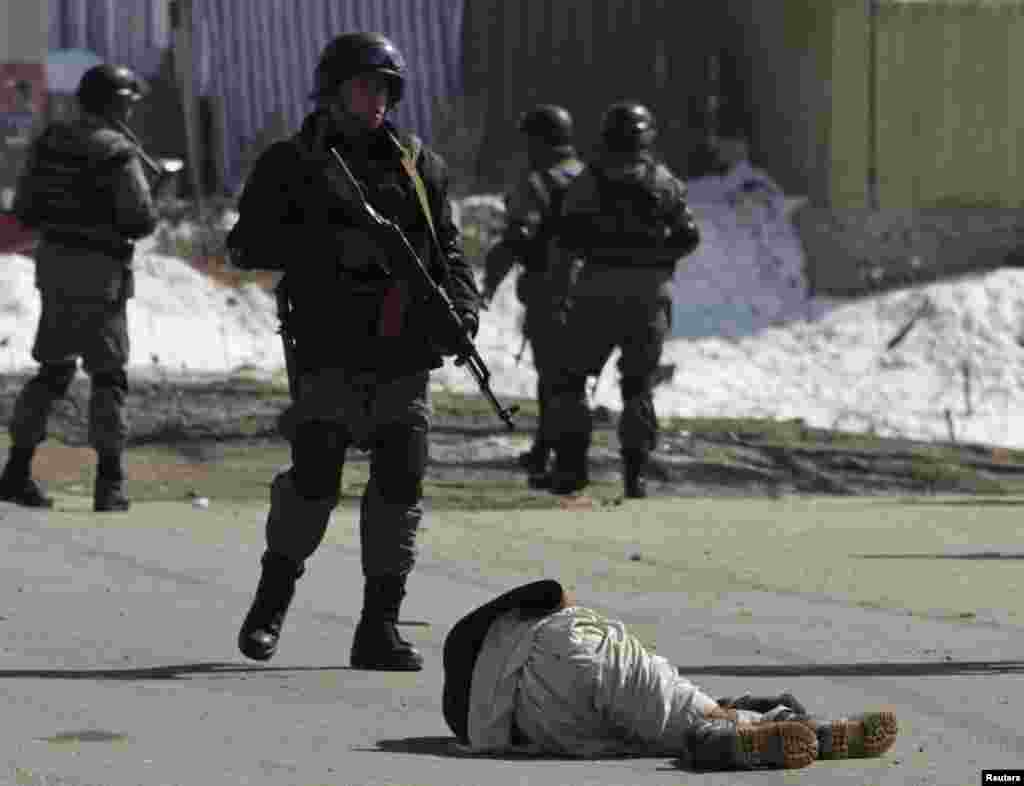 A wounded protester lies on the ground as Afghan policemen keep watch during a protest in Kabul on February 23.