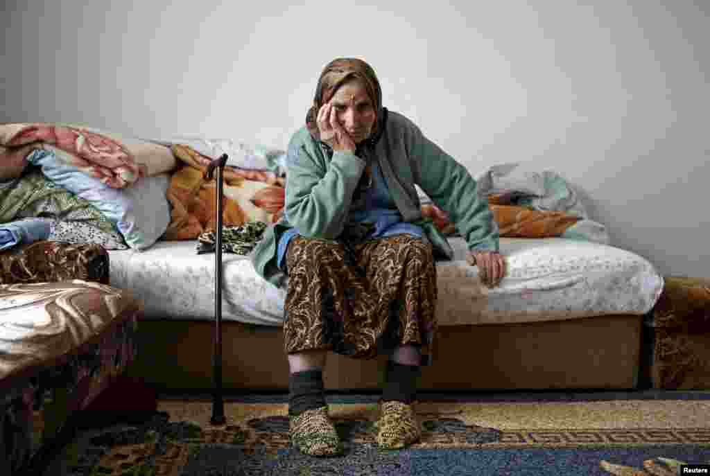 "Emina Osmanovic is seen in her home in a refugee camp near Banovici, Bosnia-Herzegovina. Emina is among several thousand women still searching for the remains of their closest relatives 20 years after the Srebrenica massacre of 8,000 Muslim men and boys. She is searching for her son. She lost 15 close family members. ""I don't know what is worse: To find his bones and know for sure that he was killed, that he is gone, or this waiting, suspense."" (Reuters/Dado Ruvic)"