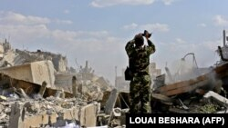 Сирийский солдат на фоне разрушенных зданий на севере Дамаска. 14 апреля 2018 года