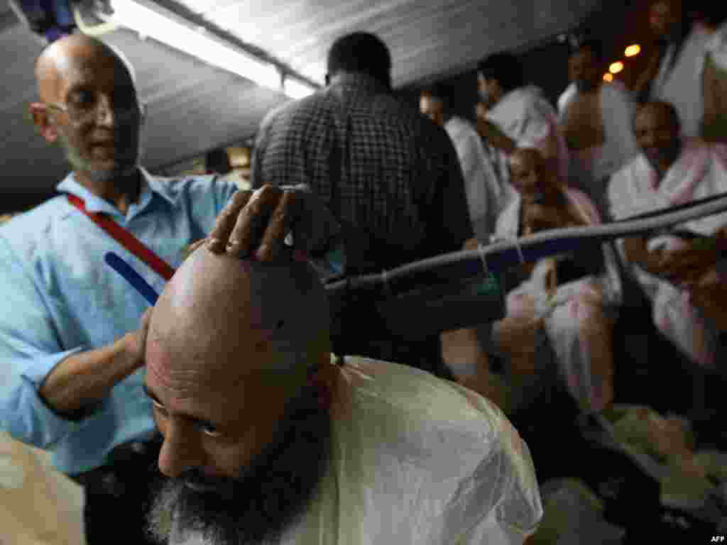 A barber in Mina shaves the head of a pilgrim after the stoning of Satan ritual. (AFP PHOTO/MAHMUD HAMS)