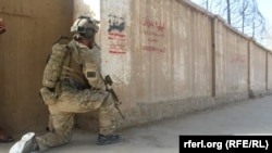FILE: An Afghan soldiers guards a building in the northern city of Kunduz.