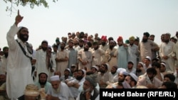FILE: In the absence of state courts, parties to a conflict often make heated arguments while making their case before a tribal jirga or council. Here, the residents of the town of Bara in the Khyber tribal district debate the fate of minority Sikhs threatened by a fanatical cleric in 2002.