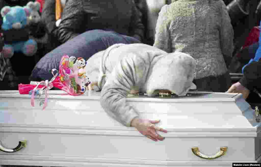 """Родственники оплакивают 10-летнюю Марию Агаркову, погибшую в пожаре в торговом центре """"Зимняя вишня""""."""
