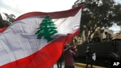 A protester waves a Lebanese flag during a protest against corruption and the failure of long-serving politicians to form a government, in Beirut, Lebanon, Thursday, Nov. 22, 2018. Lebanon is marking 75 years of independence with a military parade Thursda