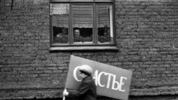 Фото Владимира Соколаева. Женщина с плакатом спешит на первомайскую демонстрацию. Новокузнецк. 1983