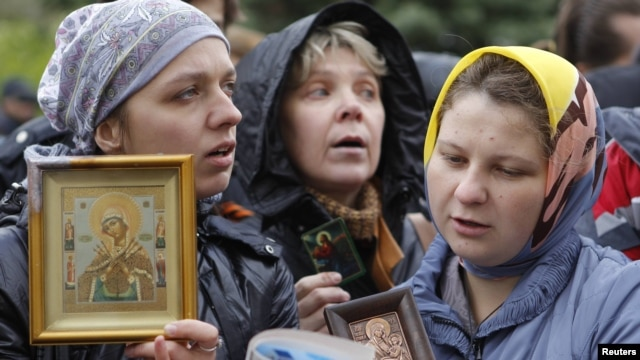 "Russian Orthodox believers gather outside a court building during the trial of members of the female punk collective ""Pussy Riot"" for hooliganism motivated by religious hatred earlier this year."