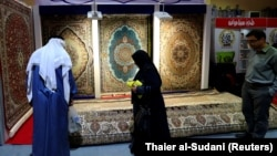 People look at the carpets displayed at the Iran section of the Baghdad International Fair, in Baghdad on November 10.