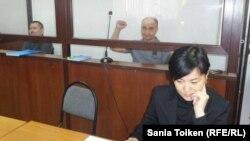 Сестра и общественный защитник Макса Бокаева Жанаргуль Бокаева (на переднем плане) на процессе, где судят ее брата (справа на заднем плане) и Талгата Аяна (слева). Атырау, 21 ноября 2016 года.
