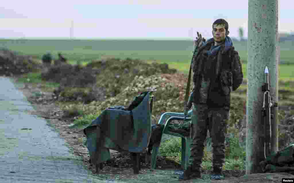 A Kurdish People's Protection Unit (YPG) fighter mans a checkpoint in Ras al-Ain, Syria.