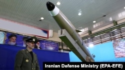 IRAN -- Iranian Defense Minister Amir Hatami stands next to a new generation of Iranian short-range missile 'Fateh-mobin' during an unveiling ceremony in Tehran, August 13, 2018