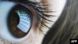 Монитор компьютера, отражающийся в глазах девушки.