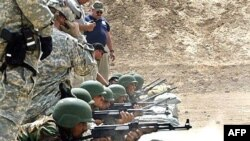 U.S. soldiers observe Iraqi police cadets shoot as they train at a firing range at a training base in the town of Hillah.