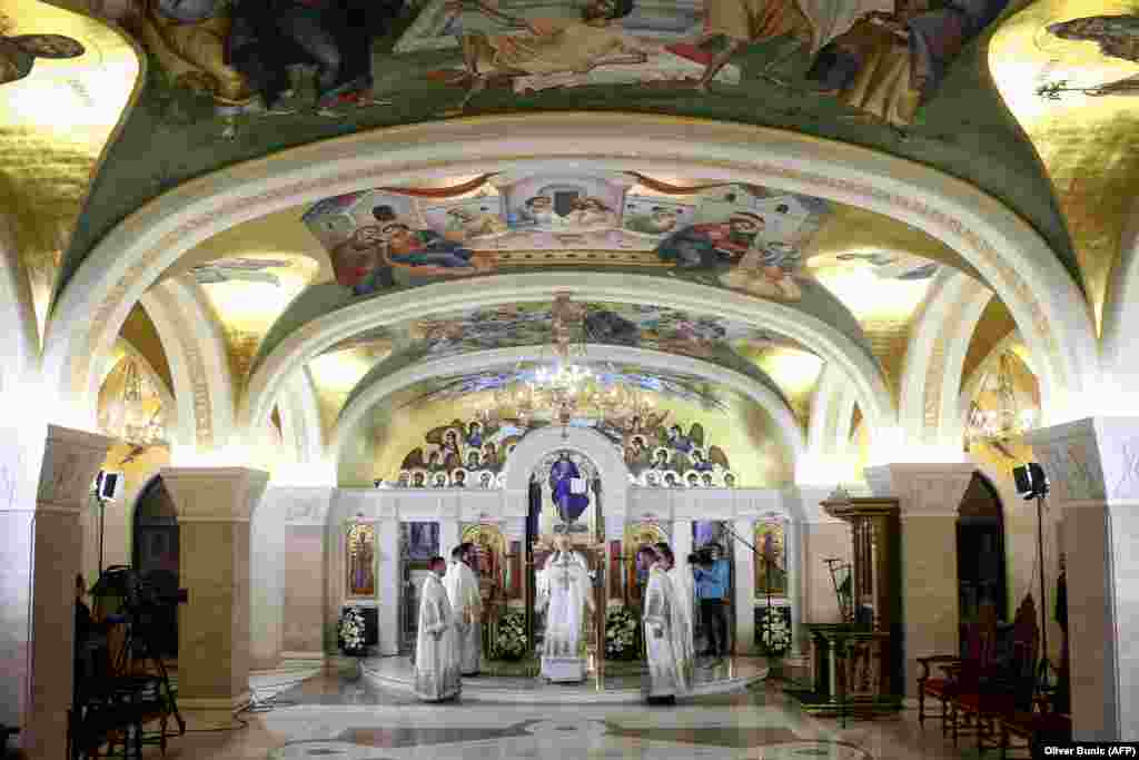 Serbian priests hold a morning Easter liturgy in the crypt of the cavernous St. Sava Temple, one of the world's largest Orthodox houses of worship, in Belgrade on April 19. Most parishioners stayed away in an effort to limit the spread of the coronavirus. In Serbia, Montenegro, and Northern Macedonia, Easter holidays were celebrated at home, without the possibility of believers attending church services.