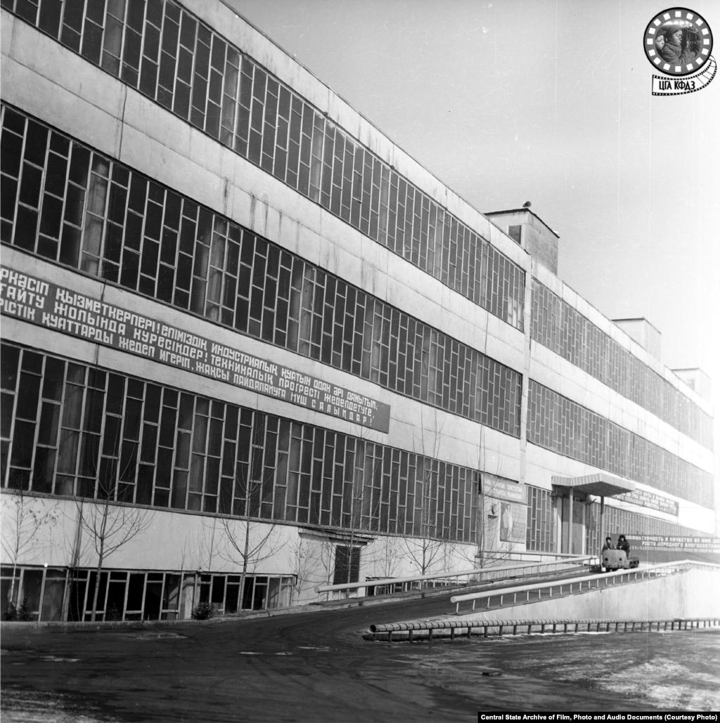 """Алматы қаласындағы №1 автокөлік жөндеу қауымдастығы ғимараты. 1977 жылы түсірілген сурет (сол жақта). Ғимарат 1930 жылы құрылған аккумулятор станциясының базасында салынды. Зауыттың негізгі корпусын 1956 жылы салып бітті. Бұл қауымдастық автобөлшектерден бөлек архитектуралық тапсырыстар бойынша жұмыс істеді. Біраз жыл Алматының негізгі көрнекі нысаныболған """"Қазақстан"""" қонақүйінің көпшілікке белгілі """"тәжі"""" осында жасалған. Қазір тозып, жартылай бос тұрған ғимаратты шағын кәсіпкерлер пайдаланып отыр."""