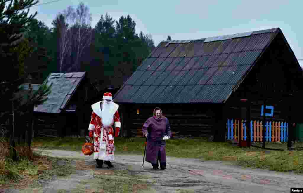 "A driver of a mobile shop, dressed as ""Father Frost"" (a Slavic equivalent of Santa Claus), helps a woman carry products that she bought on the outskirts of Minsk, Belarus, on December 23. (Reuters/Vasily Fedosenko)"