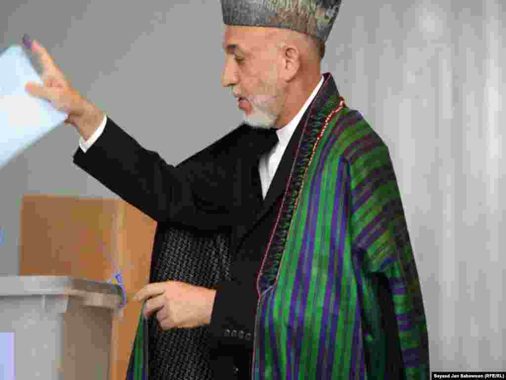 On election day, President Hamid Karzai casts his vote at a polling station in Kabul.