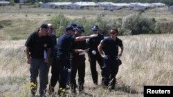 Група міжнародних експертів, включно з поліцейськими з Нідерландів, працює на місці падіння літака рейсу MH17, 1 серпня 2014 року