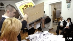 Members of a local election commission empty a ballot box in Chisinau on April 5