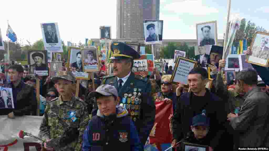 Астанада «Мәңгілік полк» шеруіне шыққандар екінші дүниежүзілік соғысқа қатысқан майдангерлер суреттерін ұстап тұр. 9 мамыр 2016 жыл.