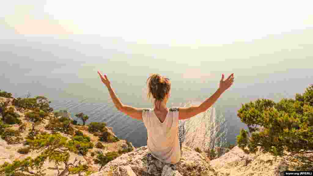 Женщина сидит на валуне горы Караул-Оба