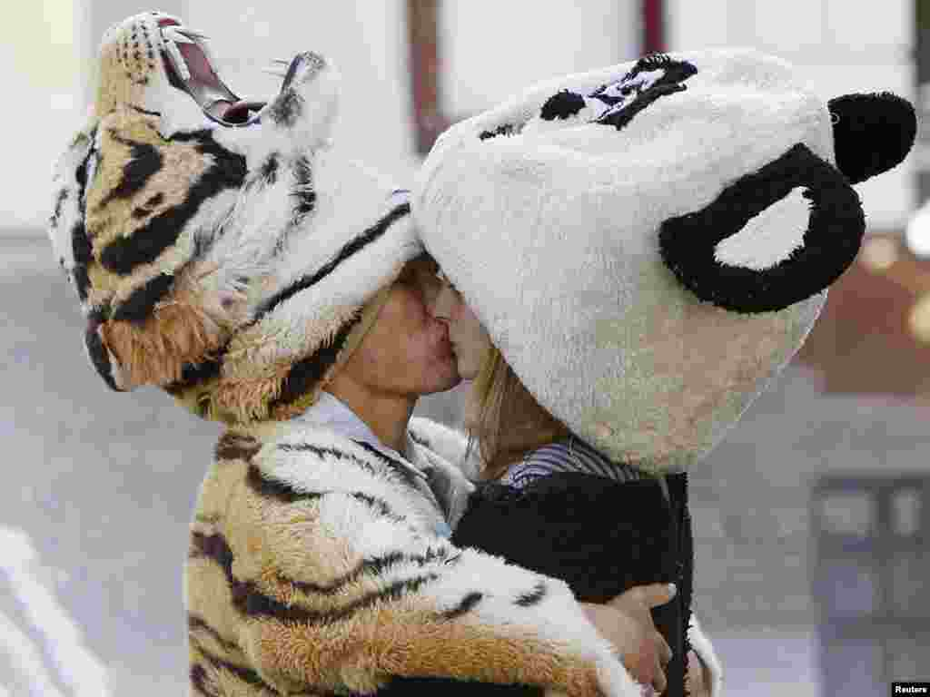 A couple, dressed as a tiger and a panda, kiss in central Kyiv on September 21. The couple sell pictures of themselves posing with tourists. Photo by Gleb Garanich for Reuters
