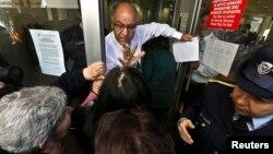 تلاش مدیر یکی از شعبههای بانکی برای آرامکردن مشتریان پیش از بازگشایی بانکها در قبرس، ۸ فروردین ۹۲