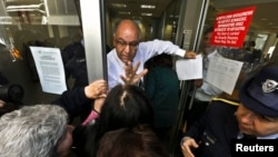 A Cypriot bank manager tries to calm depositors waiting for the bank to open in Nicosia on March 28.
