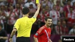 Немецкий рефери показывает российскому футболисту жёлтую карточку во время матча чемпионата Европы - 2012. Варшава, 12 июня 2012 года.