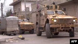 U.S. armored vehicles are seen at the scene of a suicide attack in the northern Syrian town of Manbij on January 16.