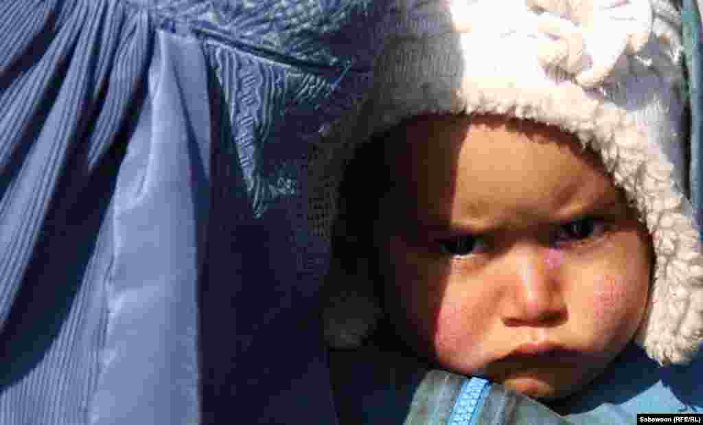 An Afghan woman holds her child as she waits to receive winter aid supplies in Kabul. (RFE/RL/Sabawoon)