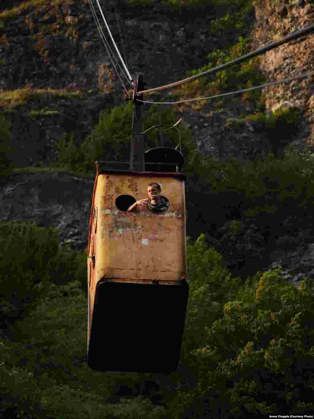 "A miner smokes a cigarette through the window of the ""Peace"" tramway which runs from the center of town up to the entrance of one of the manganese mines. The cable cars are owned by the mining company, but are open to the public."
