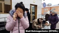 Өзін өртеп қайтыс болған Майра Рысманованың қызы Ақмарал Ахметова (сол жақта) бас прокуратура алдында жылап тұр. Астана, 14 желтоқсан 2016 жыл.