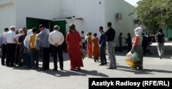 Long lines of people wait in front of a grocery store in Ashgabat to buy vegetable oil, sugar, and flour in late May.
