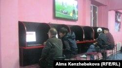 Посетители букмекерской конторы делают ставки. Алматы, 24 октября 2013 года.