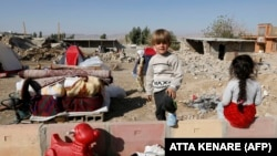 FILE: Iranians children next to the rubble of their home in Kouik village near to Sarpol-e Zahab, two days after a 7.3-magnitude earthquake struck Iran's western Kermanshah province near the border with Iraq in November.