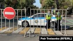 Полицейские перекрыли автомобильное движение на улице в центре Алматы, где проходит митинг. 13 сентября 2020 года.
