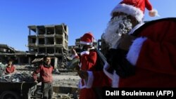 A Syrian child smiles as men dressed in Santa Claus costumes walk past destroyed buildings in the eastern Syrian city of Raqqa on December 26.