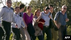 Гилад Шалиттің анасы Авива (ортада) мен әкесі Ноам (оң жақтан екінші), сондай-ақ бауыры Иоэл (сол жақтан үшінші) тікұшаққа қарай келе жатыр. Израиль, 18 қазан 2011 ж.